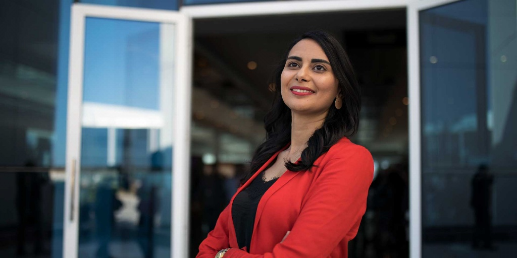 Ameni Mansouri - a brown, black-haired woman - stands outside the entrance of a glass building. She's smiling as she looks up. She's in a black top and a red blazer.
