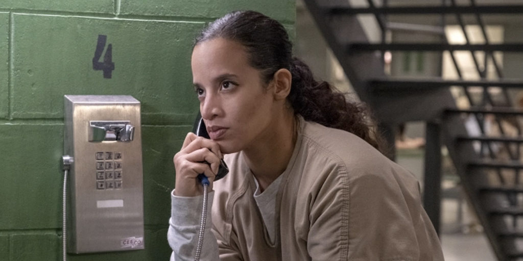 Daya, a brown woman, is on the phone, with a serious expression on her face.