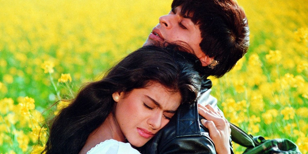 A woman with brown skin and brown hair wearing a white shirt hugs a man with brown skin and brown hair wearing a leather jacket and a camouflaged backpack.