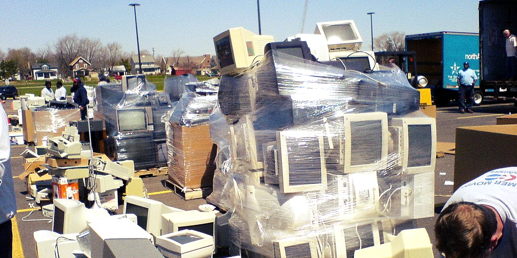 A parking lot is full of old broken computer parts. A man is seen in the right corner below a large pile of screens held together by plastic, while three other men stand in the background