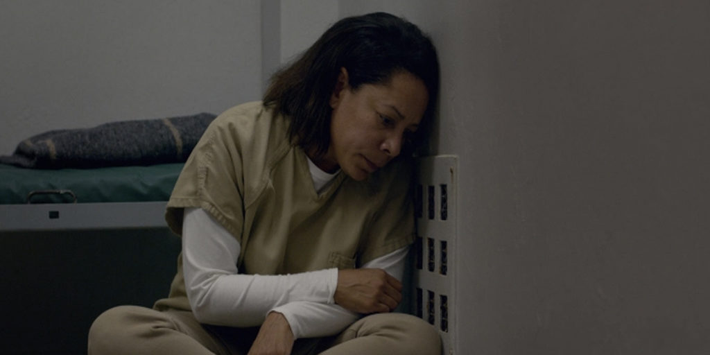 Gloria, a brown woman, is sitting on the floor in the Shu, leaning against the wall.