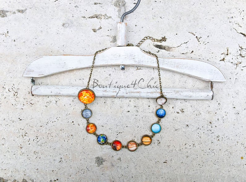 A necklace draped over a clotheshanger against an off-white background. There are ten pendants depicting the sun and nine planets.