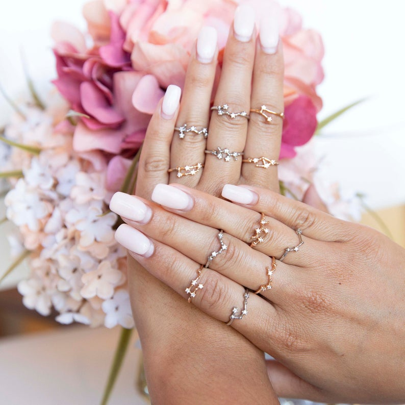 A pair of hands, one placed atop the others, with the fingers adorned by delicate metallic rings.