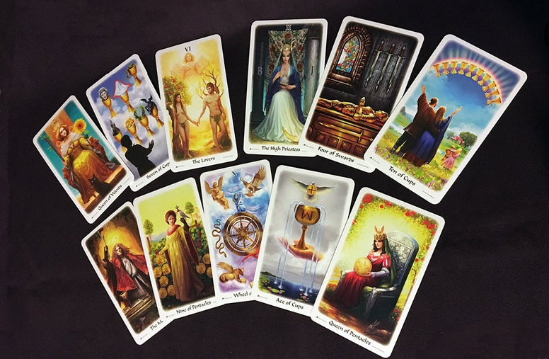 A series of colorful tarot cards spread across a black surface. Each bears an inscription of the card it is and an illustration.