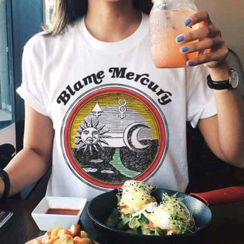 "A person with their face cropped out of the photo wears a yellow, orange and white tee shirt that says ""Blame Mercury."""