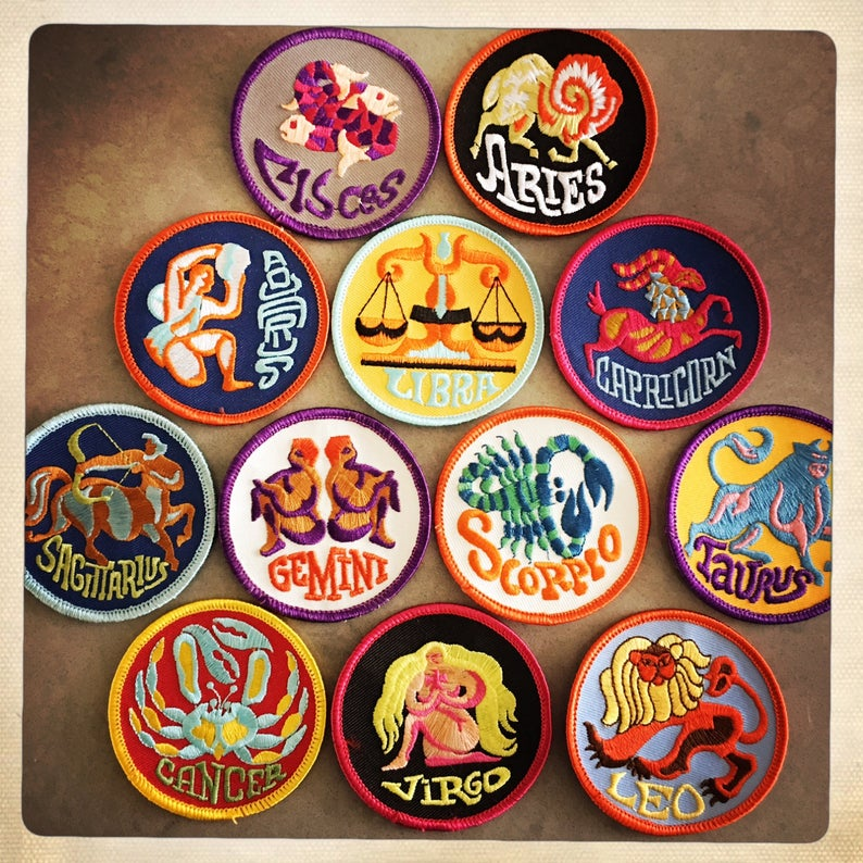 Twelve colorful patches, each with a different zodiac sign's name and symbol embroidered on it, resting on a brown background.