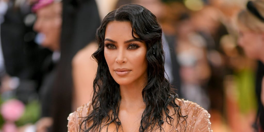 Kim Kardashian West, a white woman with dark hair wearing a nude dress at the Met Gala 2019.