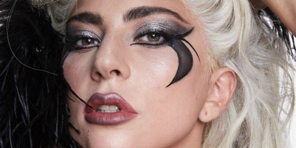 Attribute: [Lady Gaga is wearing a dramatic metallic smokey eye with graphic liner down her cheeks and purple metallic lip. She is looking at the camera.] Via Celebrity Insider.