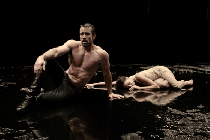 A shirtless, white man is drenched and seated on a stage. Behind him is a woman lying down.