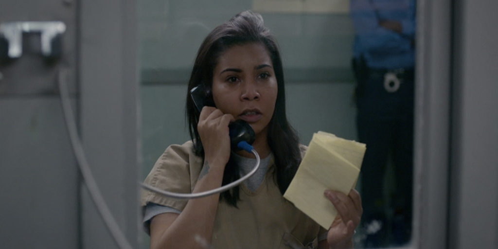 Maria, a brown woman, is holding a phone to one ear, and holding a yellow folded piece of paper in her other hand, behind glass.