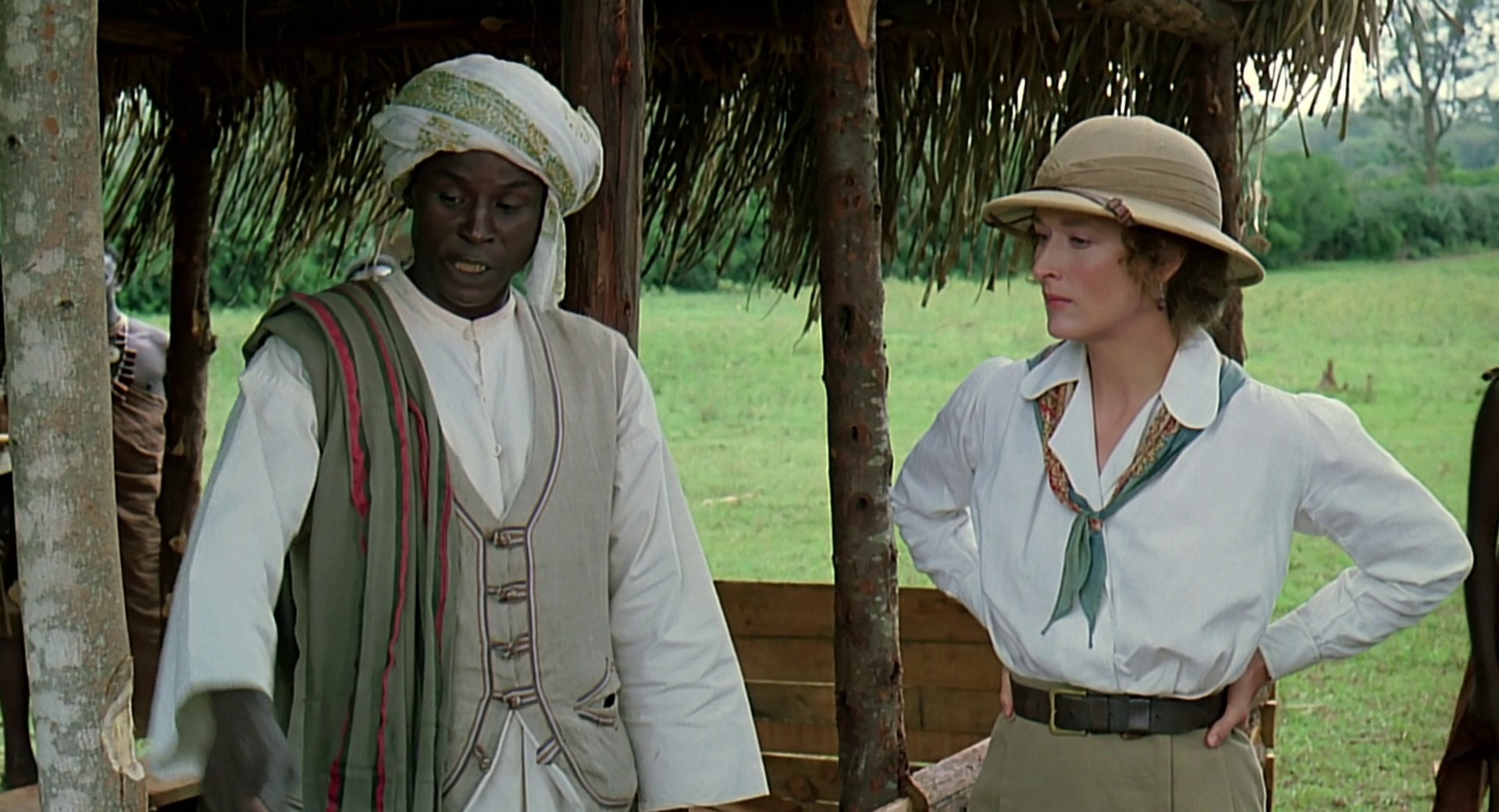 A white woman wearing a hat and white shirt with khaki pants is standing next to a black African man wearing a turban, white shirt and tan vest.