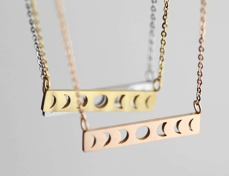 Several necklaces with pendants in colors like gold and rose gold, shaped like all the phases of the moon