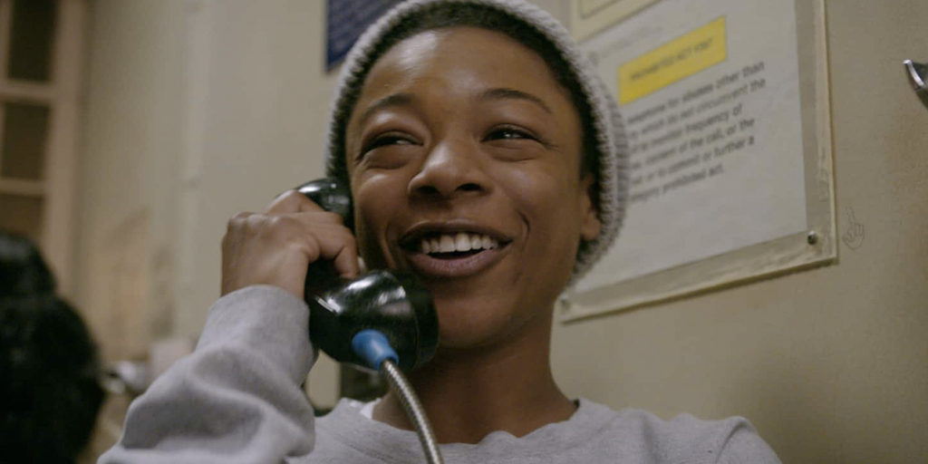 Poussey Washington, a black woman, holds a phone to one ear, and smiles.