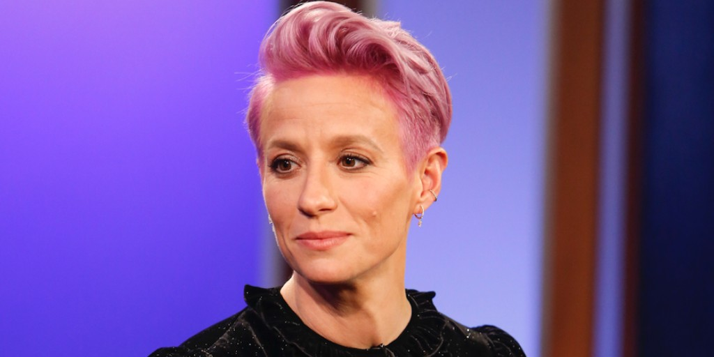 [Image description: Megan Rapinoe in black shirt with trademark pink hair.] Via Getty Images.