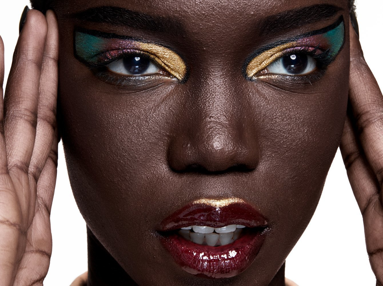 Attribution: [Nyajock, a black female model, is wearing a deep red lip gloss with a hing of gold. She is wearing gold, purple, and green eye shadow inside winged graphic eyeliner. She is looking into the distance.] Via Haus Labs.