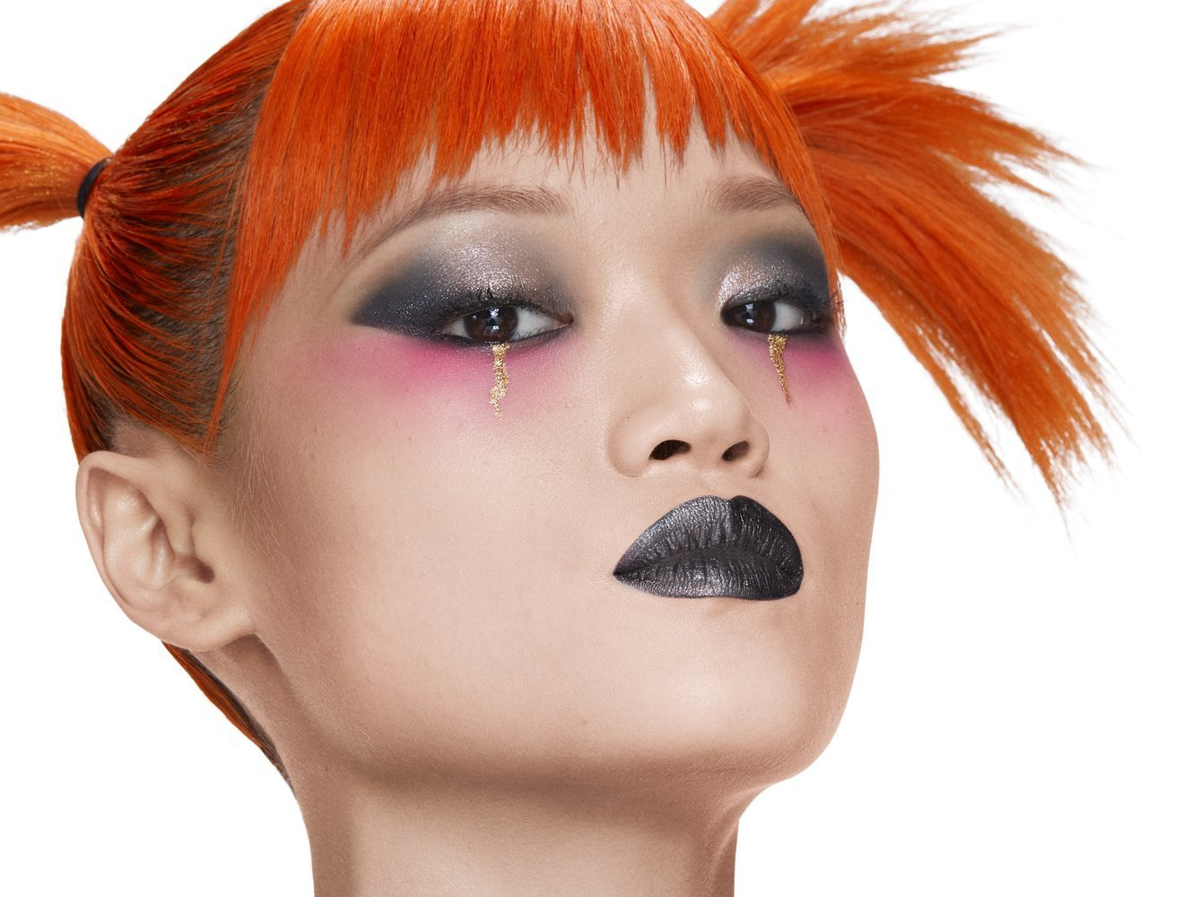 Attribution: [Kitty, an Asian model, is wearing a silver and black eye shadow with pink eye shadow under her eyes and golden tear drops. She is wearing black shimmer on her lips and her orange hair is in pig tails. She is looking solemnly into the camera.] Via Haus Labs.