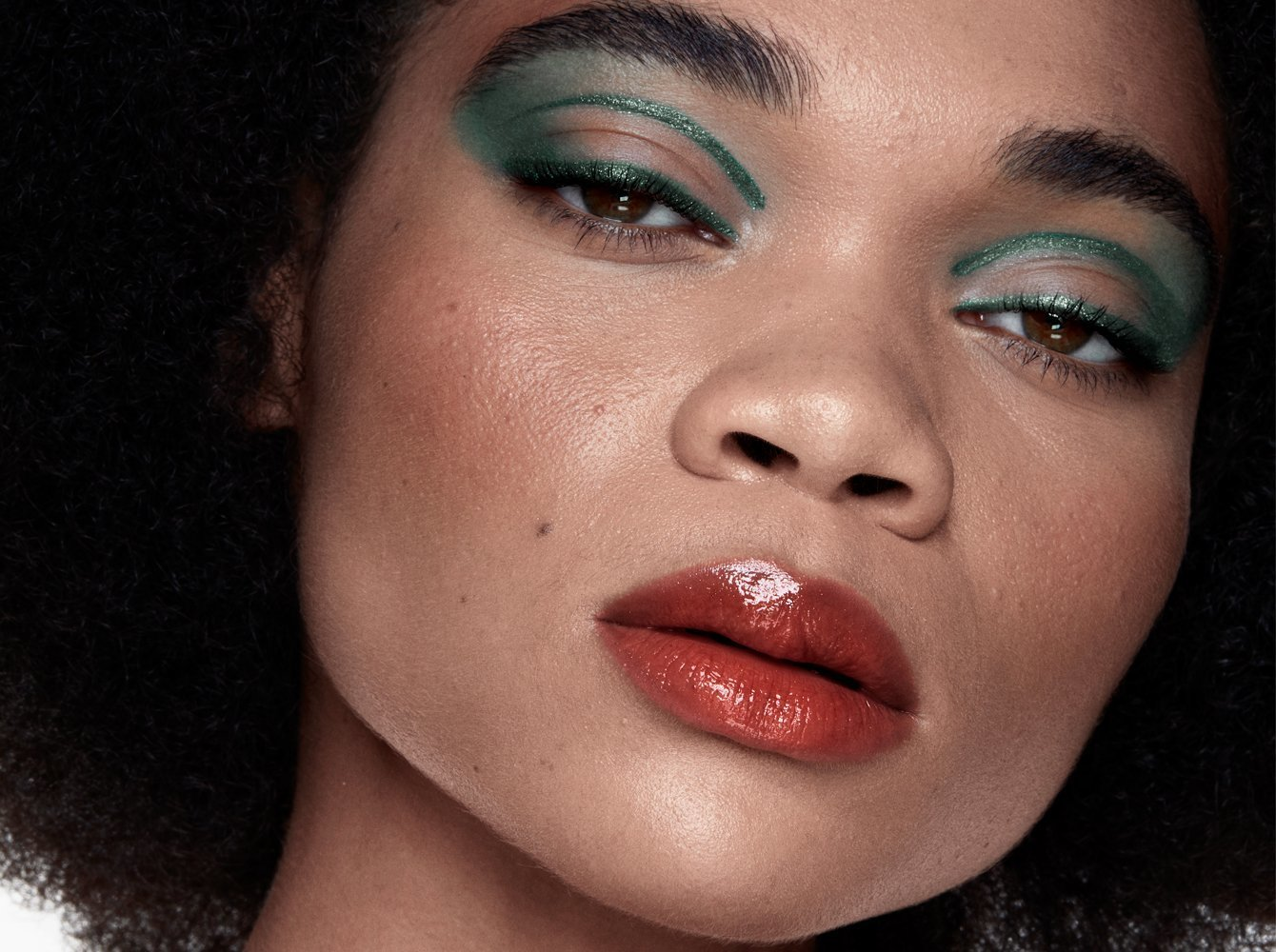 Attribution: [Chavi, a black female model, is wearing green eye shadow and crimson lip gloss. She is looking solemnly at the camera.] Via Haus Labs.