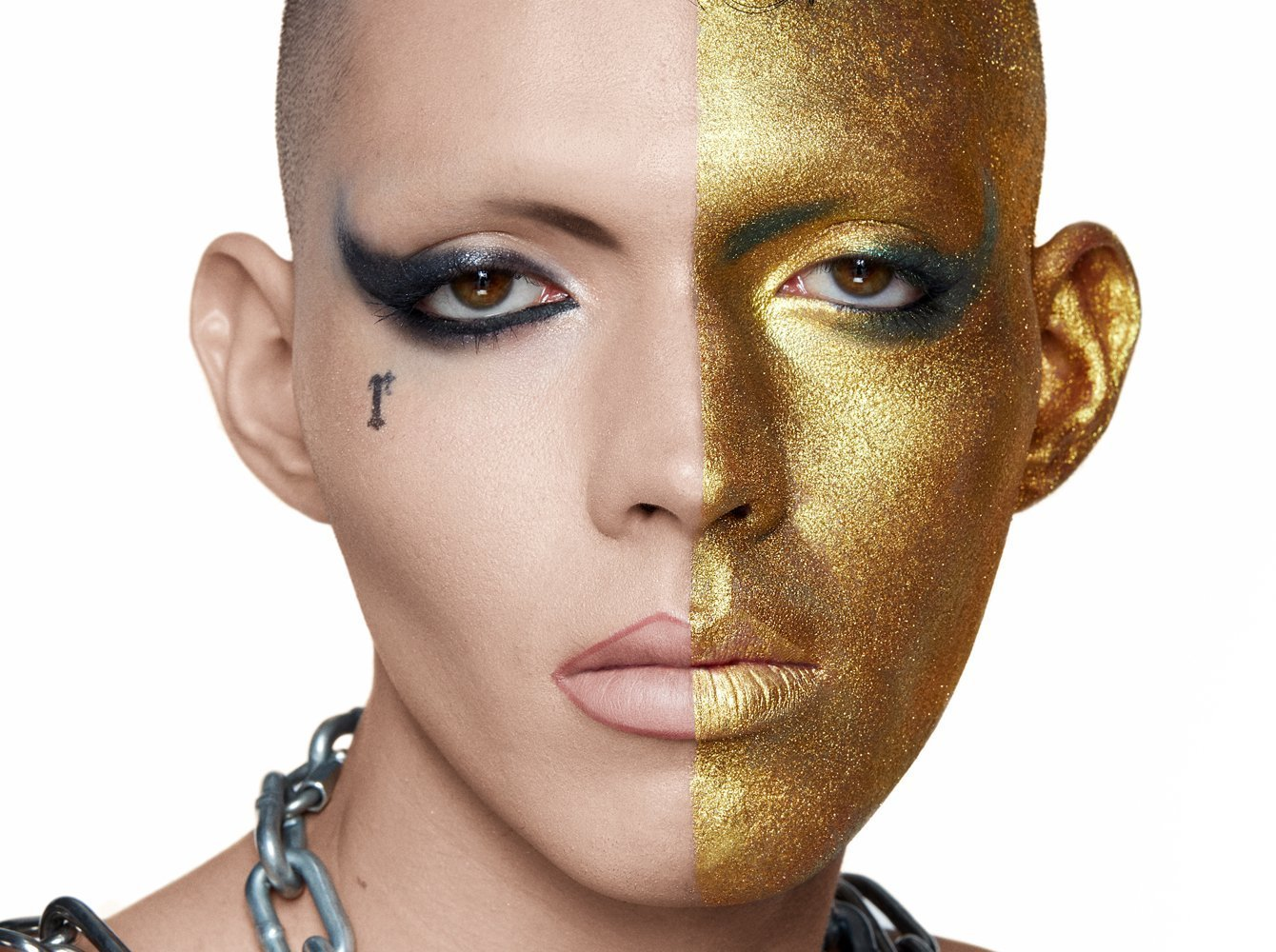 Attribution: [Fish, a black male model is wearing dramatic winged eyeliner on both eyes and half of his face is covered in gold eye shadow. He is looking solemnly at the camera.] Via Haus Labs.