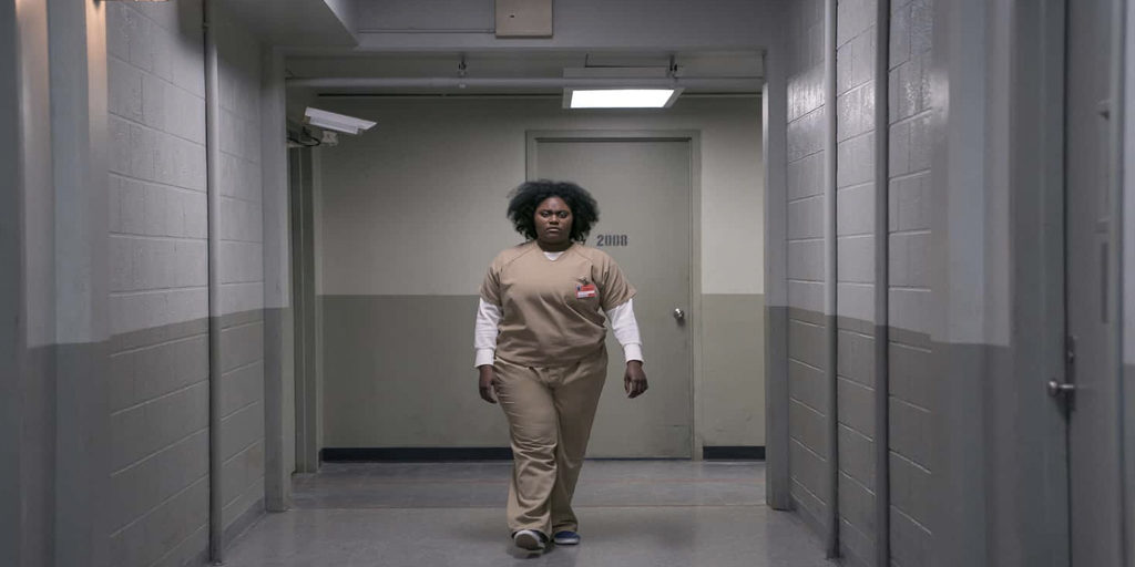 Taystee, a black woman with black curly hair, walking down the Litchfield hallway in her uniform wearing a distraught expression.
