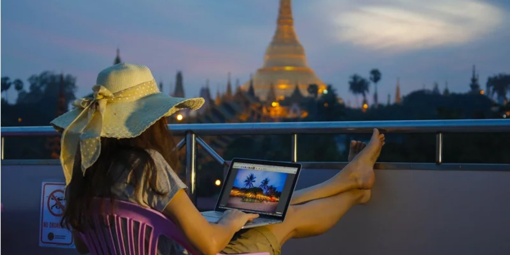 a woman with long brown hair in a sun hat watches the Shwedagon Pagoda in Yangon, Burma while working on her laptop.
