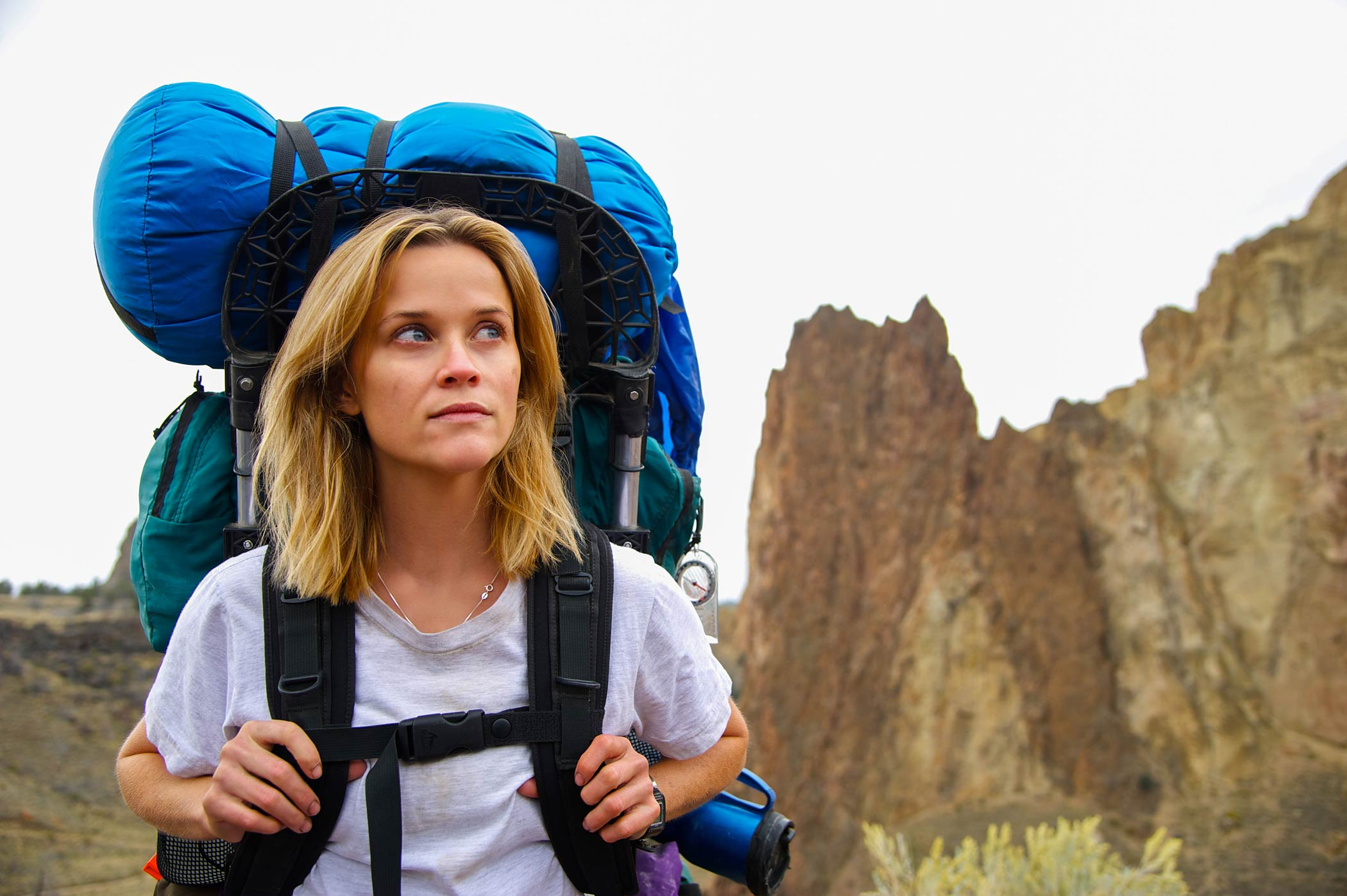Reese Witherspoon, a white woman with blonde hair, is wearing a grey shirt and carrying a large hiking backpack while standing on a mountainous trail. She is looking into the distance.
