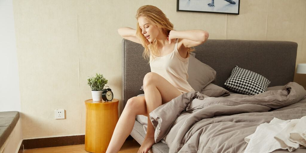 An image of white woman waking up in a minimal bedroom yawning and stretching her arms.] Taken by @iyumnai via Unsplash