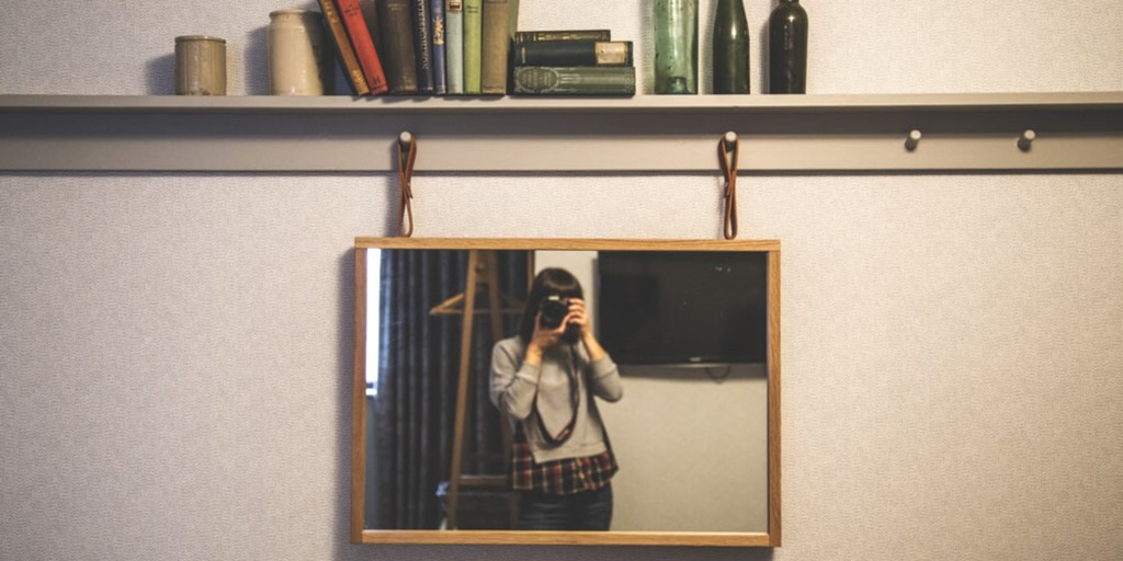 A brunette woman stands in front of a mirror and takes a picture of herself.