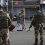 [image description: a group of soldiers face away from the camera as they crowd around an old man.] via Human Rights Watch (https://www.hrw.org/news/2019/08/06/india-basic-freedoms-risk-kashmir)