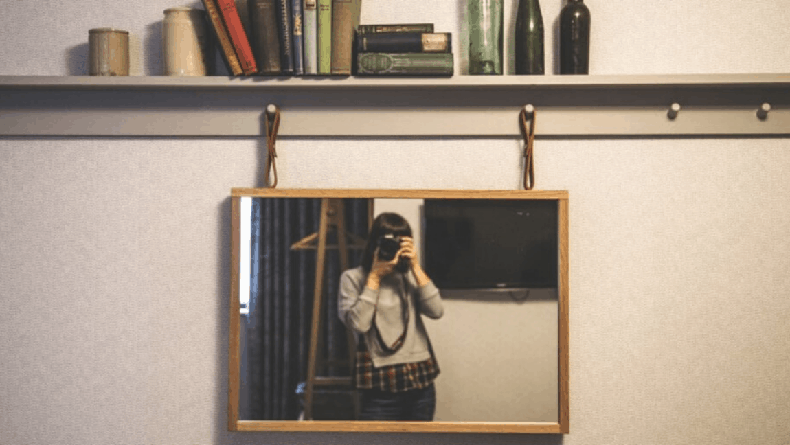 [Image description: A brunette woman stands in front of a mirror and takes a picture of herself.] Via Unsplash