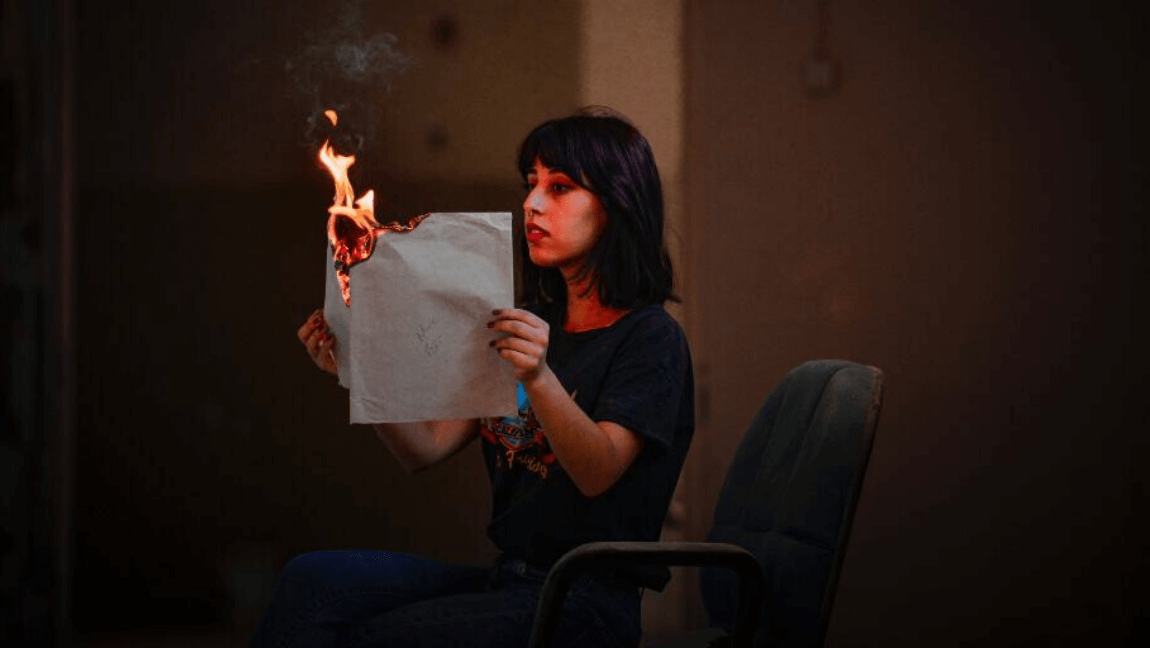 [Image description: A dark-haired woman is seated in a large, dark, and somewhat dilapidated room. She's holding a large sheet of paper between her hands, reading it, and it's slowly burning.] Via osman alyaz on Pexels