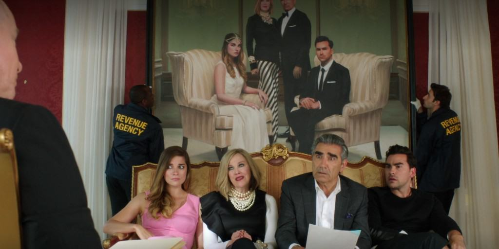 An image of the cast of Schitt's Creek on a sofa in talks with someone repossessing their belongings.