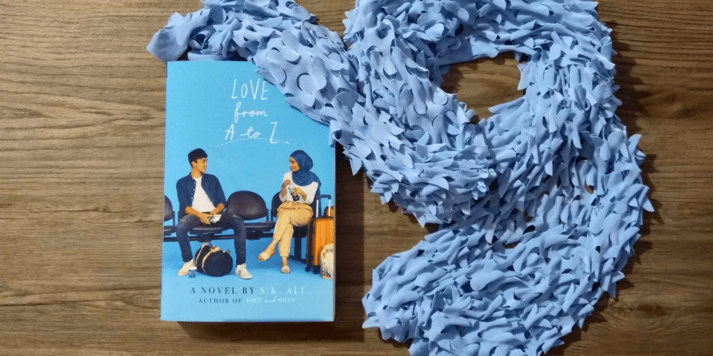"A blue scarf is next to the book ""Love from A to Z"" on a wooden table."