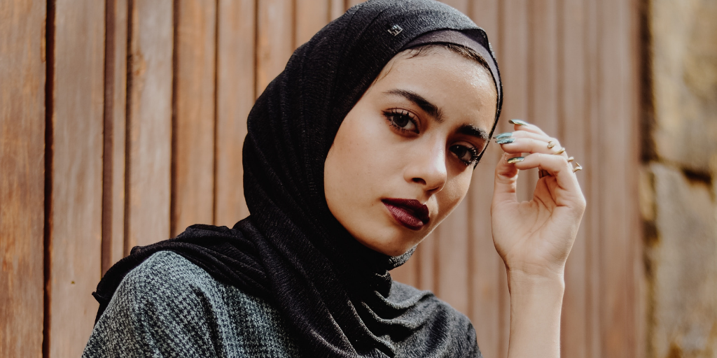 [Image description: Woman wearing a headscarf stares into the camera.] Photo by Mohammed Hassan on Unsplash