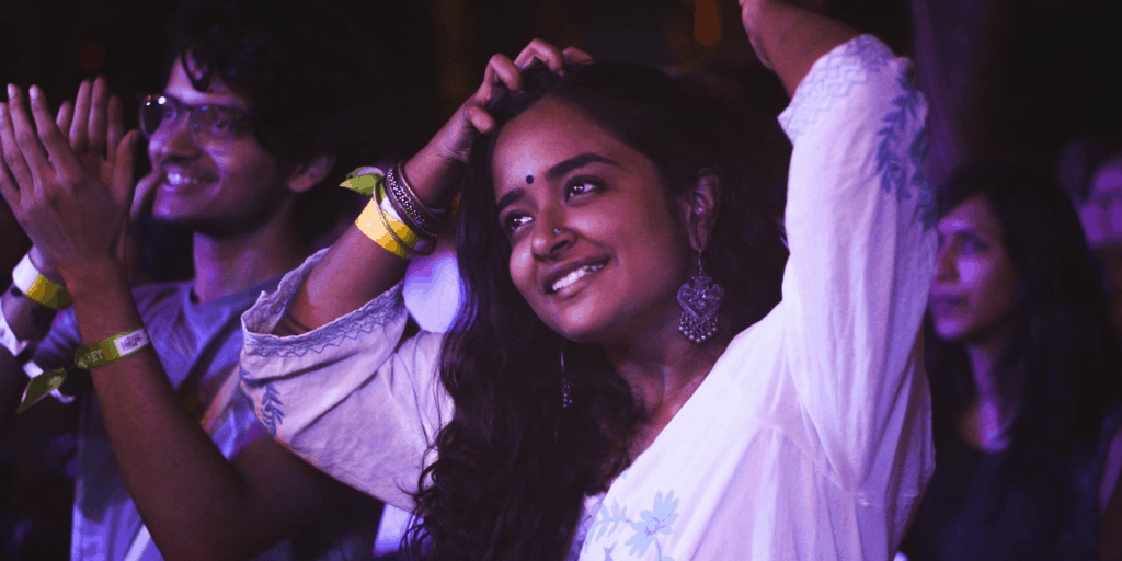 [Image Description: A woman of South Asian descent smiling with her hands above her head, and a man of South Asian descent clapping behind her as if they are both watching something] via Unsplash