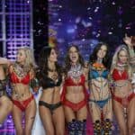 Eight models in lingerie are celebrating on a catwalk with their arms around each other