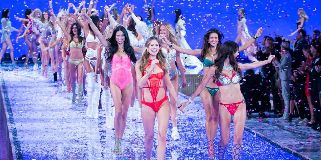 Models are in pairs and walking down a catwalk smiling and cheering in lingerie as confetti falls down around them.
