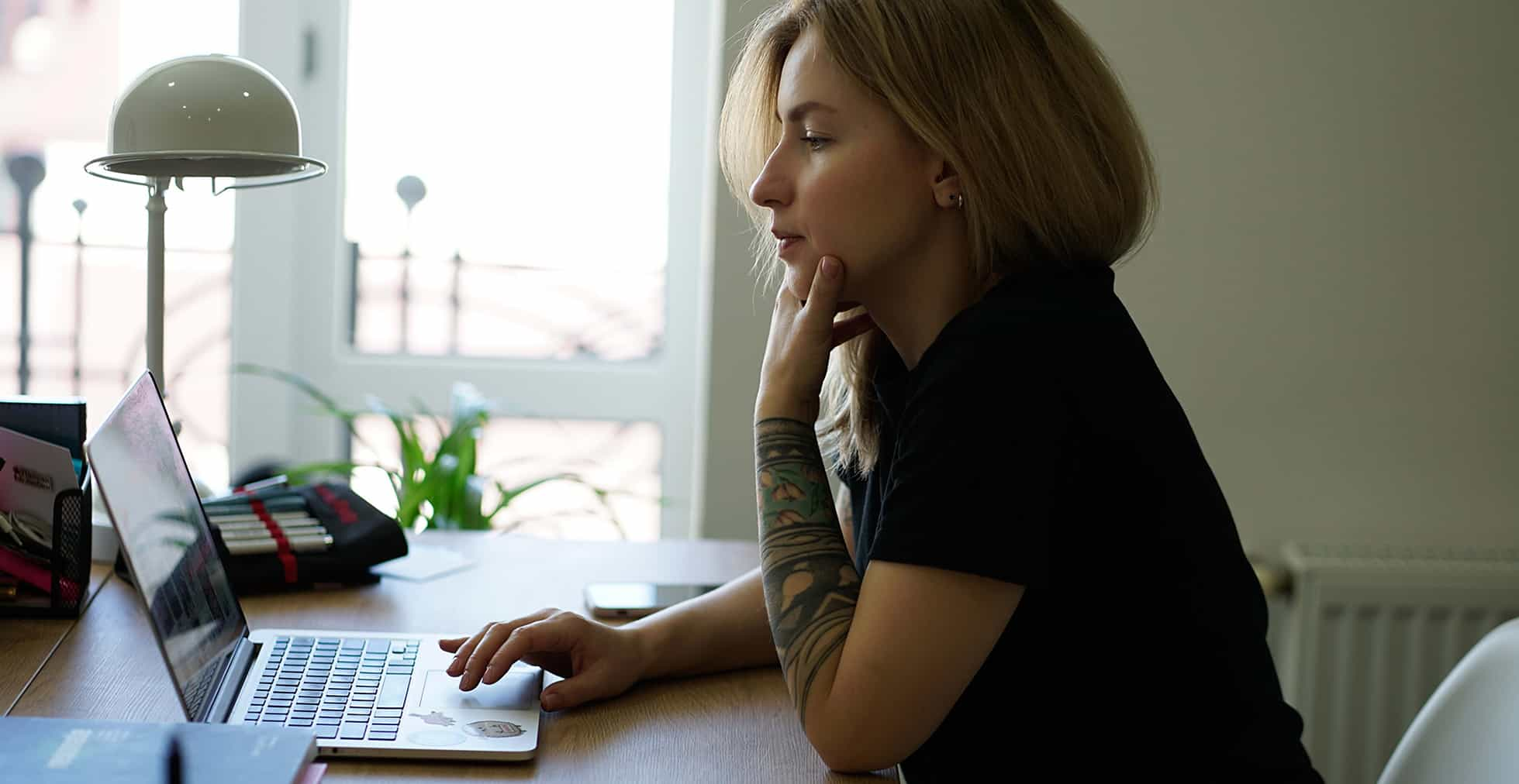 Woman with pale skin and blonde hair looking pensively at a computer