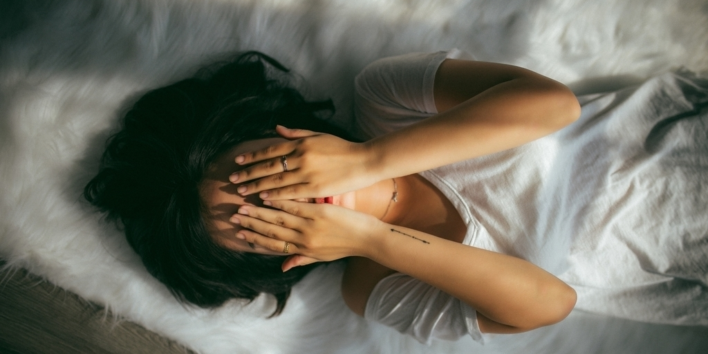image description: a girl with short black hair wearing a white t shirt is seen from above lying on a white rug and covering her face with her hands