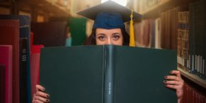a white girl with brown hair wearing a blue graduation cap is standing in a library and holding a green book over half of her face. She is looking at the camera
