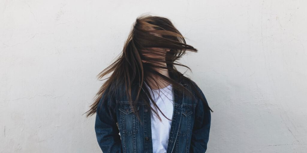 A brown haired woman in a white top and dark blue denim jacket stands before a grey wall with her hair all over her face