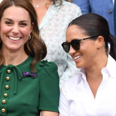 [Image description: The Duchess of Cambridge is wearing a green dress and smiling. The Duchess of Sussex is to her left, wearing a white shirt and sunglasses and smiling.] Via Karwai Tang/Getty Images.