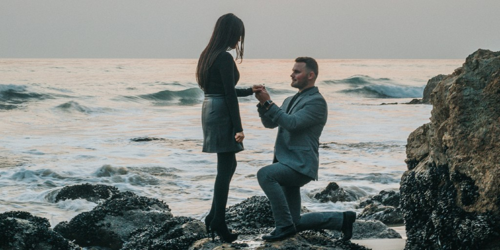 A white man wearing a suit is down on one knee, proposing to a brunette, white woman.