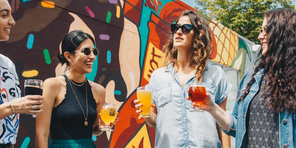 A group of four women in conversation stand against a vibrant background with drinks in hand.
