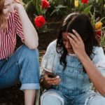 A girl with brown skin and black hair is seated on the ground looking at her phone. She is wearing denim overalls and behind her are red and yellow flowers. On the left of the image, two of her friends, both with white skin and brown hair, also look over at her phone.