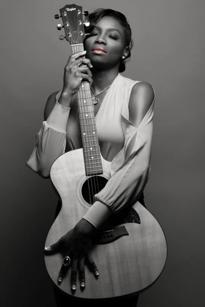 image description: a black and white picture of Myoa with only her lips showing a peach color she is wearing a white top and hugging a guitar