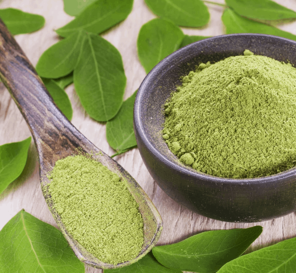 A spoonful of lime green powder is shown next to a bowl full of it, atop darker green leaves.