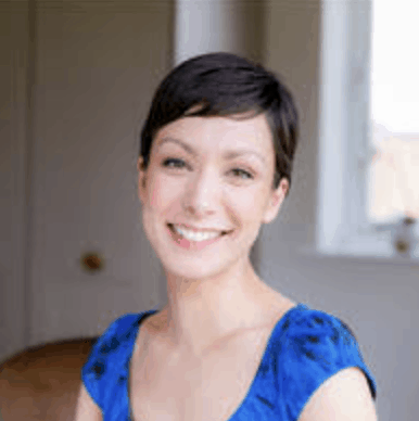 Anna Iveson, a woman with short, dark hair, smiles at the camera. She is wearing dark blue top.