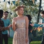 [Image description: A white, blonde teen smiles sweetly as she is admired by other teens in mask. She is in a white-gold sequined dress and a flower crown.] Via The A List Official on YouTube