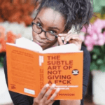 [Image description: A black woman is sitting in front of rows of potted plants. In her right hand, she holds a copy of The Subtle Art Of Not Giving A F*ck. Her left hand is on the hinge of her glasses.] Via blackandbrownlove on Tumblr