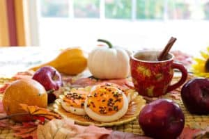 [Image Description: A photo of a Fall spread including hot apple cider, cookies and small pumpkins.] Via Pixabay